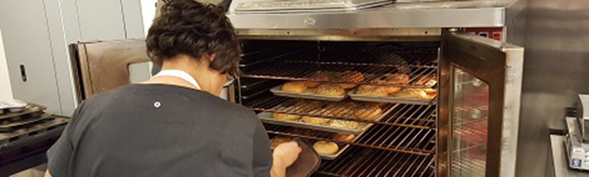 community and continuing education student taking bagels out of oven