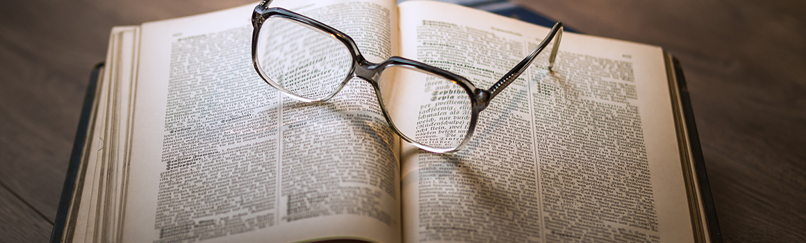 eyeglasses perched on top of open book
