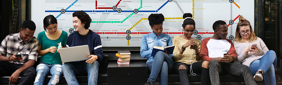 people sitting on a bench at a bus stop, with a transit map on the wall behind them