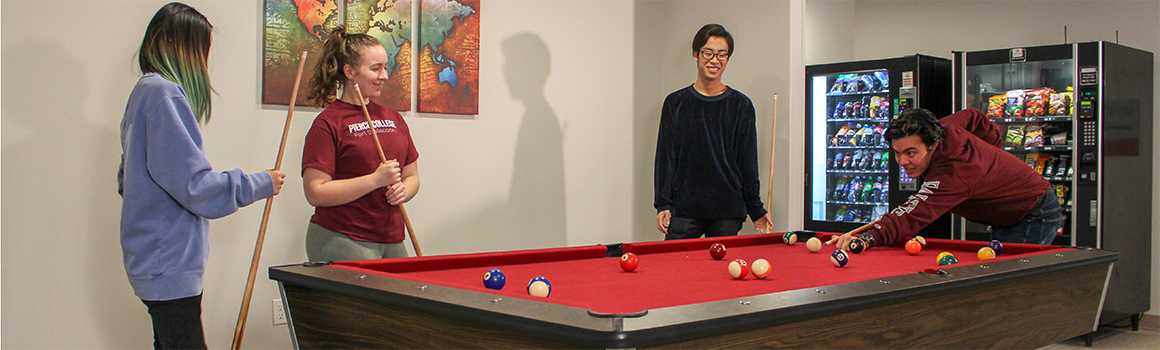 students playing pool in the residence hall