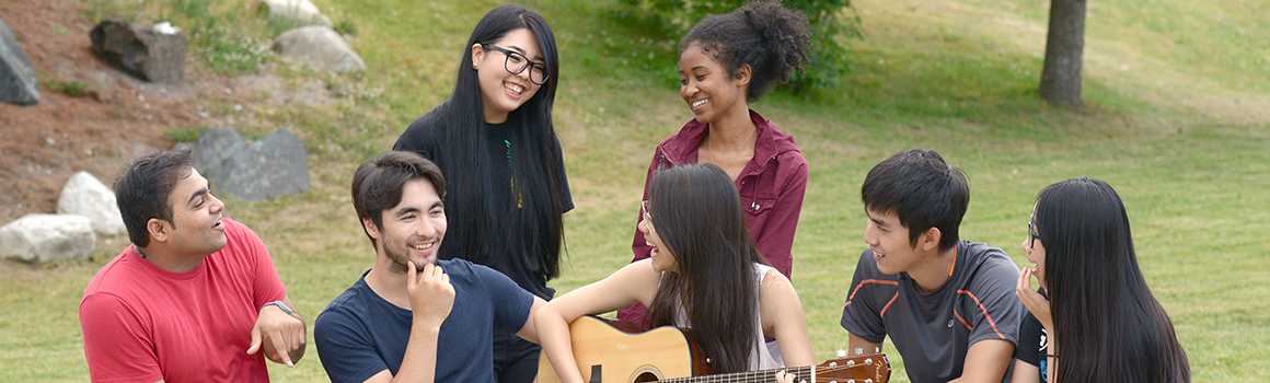 group of students sitting outside with guitar
