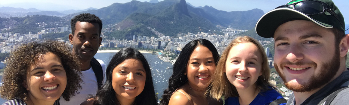 group of smiling students with view of brazil in background on a sunny day