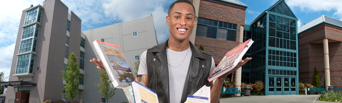 smiling student standing in front of jblm buildings dropping textbooks
