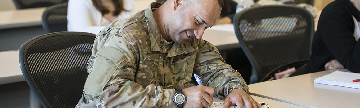 student in military attire smiling and completing paperwork at a desk