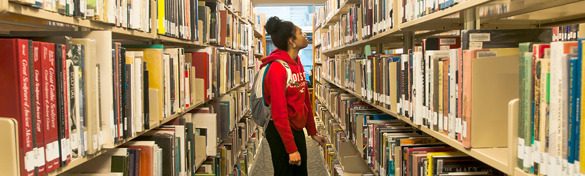 student browses through library books