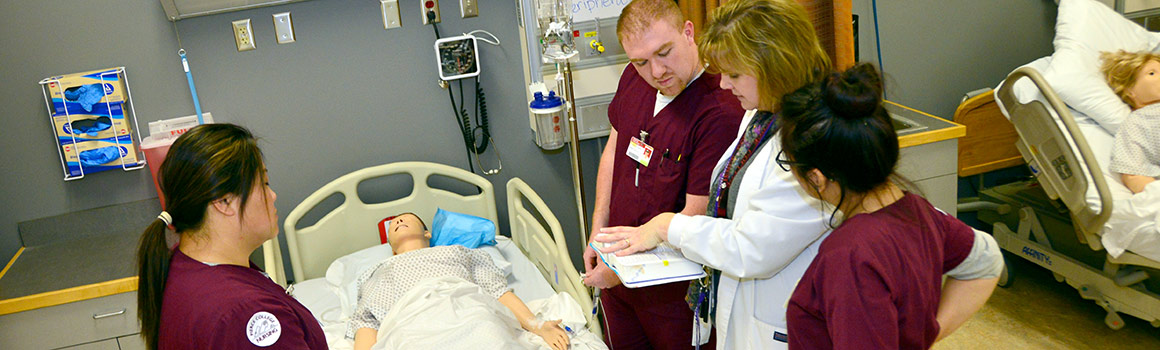 nursing students and instructor practicing with a pretend patient
