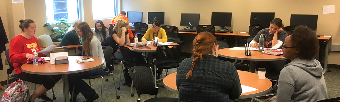 students and tutors working at tables in writing center