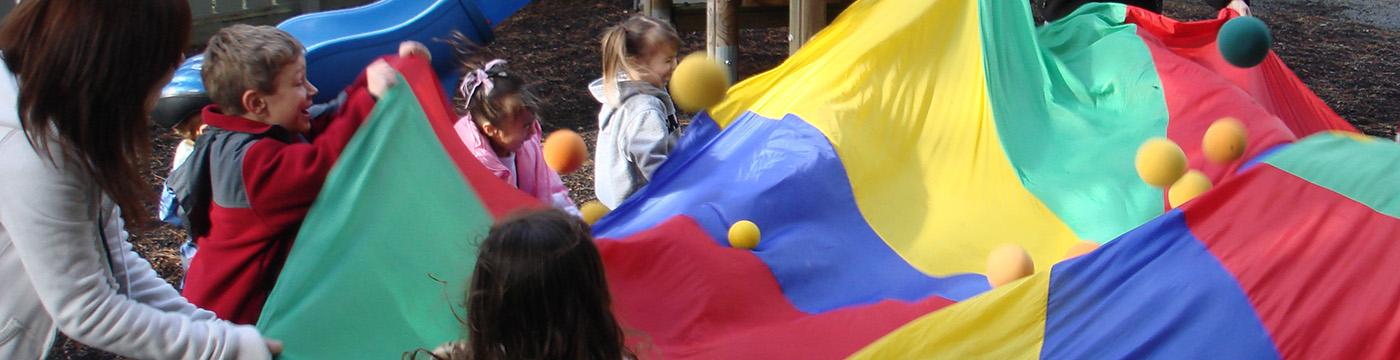 adult and children playing with a large canvas and balls