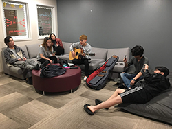 students playing guitar in the lounge