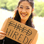person holding sign that has the word fired crossed out and the word hired replacing it