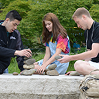 Students stacking rocks outside the College Center Building