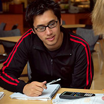 student at desk with pen and calculator