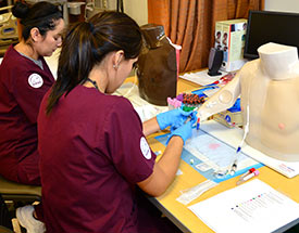 two women in scrubs practicing with IVs