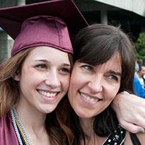 daughter in graduation attire hugging mother