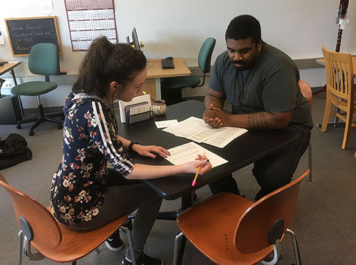 student and tutor working together at table in puyallup writing center